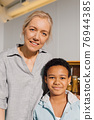 Woman standing at the kitchen with her multiracial son and embracing 76944385
