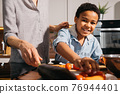 Boy stretching for the pepper while helping to his mother preparing food 76944401