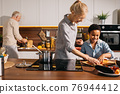 Woman teaching boy cooking, while helping chopping vegetables for dinner 76944412