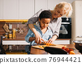 Mother teaching her little son holding knife and cut fresh vegetables in kitchen 76944421