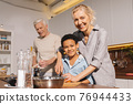 Happy multiracial family standing at the table while cooking at the kitchen 76944433