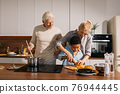 Mother teaching her little son holding knife and cut fresh vegetables in kitchen 76944445