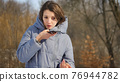 Lady in blue coat is sending audio voice message explaining something on smart phone at outdoor talking to mobile assistant. Girl using smartphone voice recognition and dictation 76944782