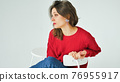 Studio portrait of young woman in red knitted sweater and earring sitting on a chair on white background 76955917