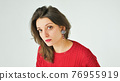 Studio portrait of young woman in red knitted sweater and earring on white background 76955919