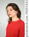 Studio portrait of young woman in red knitted sweater and earring on white background 76955932
