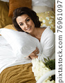 Attractive smiling brunette hugging pillow on bed. 76961097