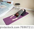 Woman doing asanas on yoga mat near bed 76967211