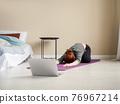Woman doing asanas on yoga mat near bed 76967214