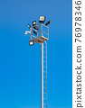 Pole with spotlights and CCTV camera at a ski resort. 76978346