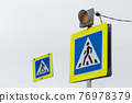 Road sign white triangle with a man in a blue square means a pedestrian crossing 76978379