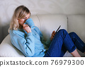 Woman on the couch with coffee mug and cell phone 76979300