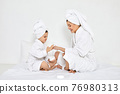 mother and daughter in white bathrobes apply cream 76980313