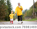 Rainy day Mother and little daughter walking after rain dressed yellow raincoat 76981469