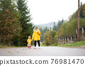 Rainy day Mother and little daughter walking after rain dressed yellow raincoat 76981470