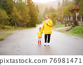 Rainy day Mother and little daughter walking after rain dressed yellow raincoat 76981471
