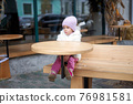 Unhappy little girl sitting outdoor cafe at table autumn season Caucasian female child losy in city sitting sad 76981581