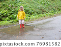 Playful girl wearing yellow raincoat while jumping in puddle during rainfall 76981582