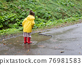 Playful girl wearing yellow raincoat while jumping in puddle during rainfall 76981583