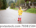 Playful girl wearing yellow raincoat while jumping in puddle during rainfall 76981584