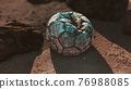 Old leather soccer ball abandoned on sand 76988085