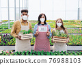 People working in greenhouse in garden center, store open after coronavirus lockdown. 76988103
