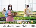 People working in greenhouse in garden center, store open after coronavirus lockdown. 76988106