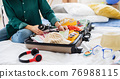 Unrecognizable woman with suitcase packing for holiday at home, coronavirus concept. 76988115