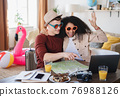 Young couple with laptop packing for holiday at home. 76988126