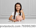 Little child girl with piggy bank at home 76990280