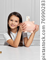 Little child girl with piggy bank at home 76990283