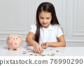 Little child girl with piggy bank at home 76990290