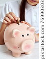 child girl putting coin into pink piggy bank. 76990303