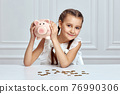 Little child girl with piggy bank at home 76990306