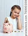 Little child girl with piggy bank at home 76990309
