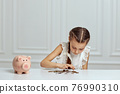 Little child girl with piggy bank at home 76990310