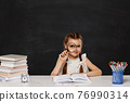 cute schoolgirl sitting at table with magnifying glass 76990314