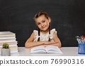 little child girl reading a book in the classroom 76990316