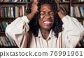 Stressed Afro-american businesswoman raises hands in despair 76991961