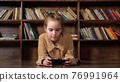Interested schoolgirl plays online game on black smartphone 76991964