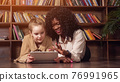 Black lady with curly hair looks into tablet display by girl 76991965