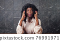 Worried black lady holds crossed fingers of trembling hands 76991971