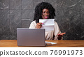 Afro-american businesswoman opens envelope and enters code 76991973