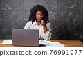 Afro-american businesswoman talks on phone looking at graphs 76991977