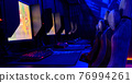 Inside of illuminated internet cybercafe 76994261