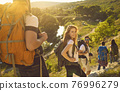 Smiling traveling woman with friends in mountains 76996279