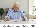 Elderly man worker finding information in internet on tablet and writing down in notebook 76996285