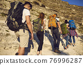 Group of young hikers with backpacks climbs a mountain trail up on a sunny day. 76996287