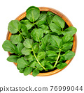 Watercress leaves in a wooden bowl. Fresh yellowcress, Nasturtium officinale. Leaf vegetable with piquant flavor. Aquatic vegetable or herb. Close-up from above, isolated over white, macro food photo. 76999044