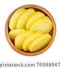 Cooked and sliced potatoes, in a wooden bowl. Boiled and peeled waxy potatoes, cut into thick slices. A side dish or for a salad. Close-up, from above, isolated on white background, macro food photo.  76999047